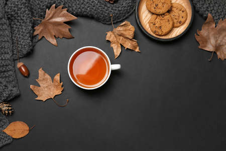Flat lay composition with hot cozy drink and autumn leaves on dark background. Space for text