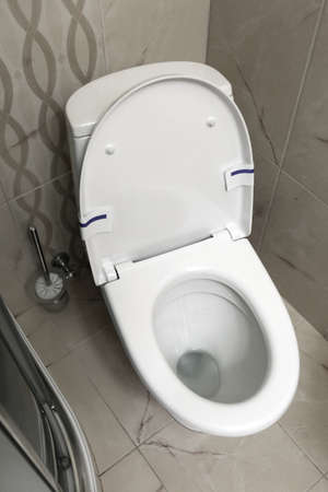 Modern white toilet bowl with seat in bathroom, above view