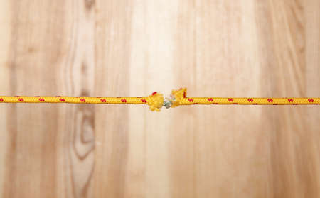 Frayed rope at breaking point on wooden background