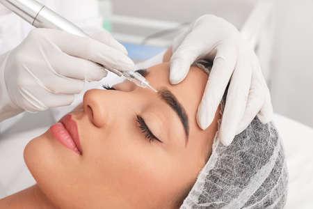 Giovane donna sottoposta a procedura di trucco permanente del sopracciglio nel salone del tatuaggio, primo piano
