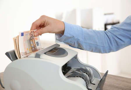 Female teller putting money into currency counting machine at cash department, closeup