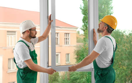 Construction workers installing new window in house