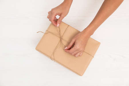 Woman decorating parcel with twine on wooden background