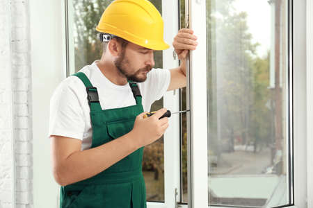 Construction worker installing new window in house