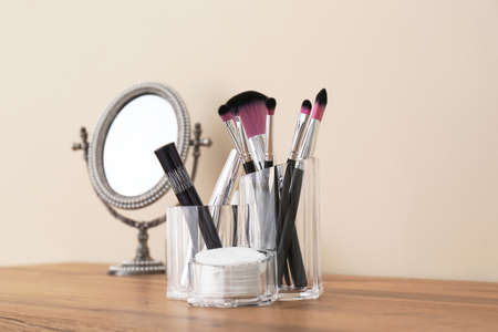 Organizer with cosmetic products for makeup and mirror on table against light wall 免版税图像 - 111051914