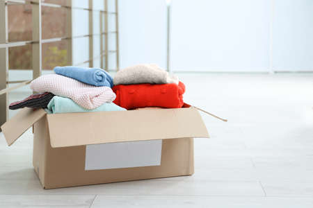 Donation box with clothes on floor indoors. Space for text Stock Photo