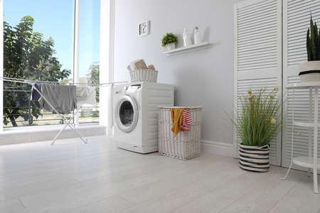 Wnętrze pralni z pralką przy ścianie