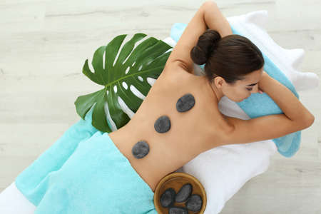Beautiful young woman getting hot stone massage in spa salon, top view Stock Photo