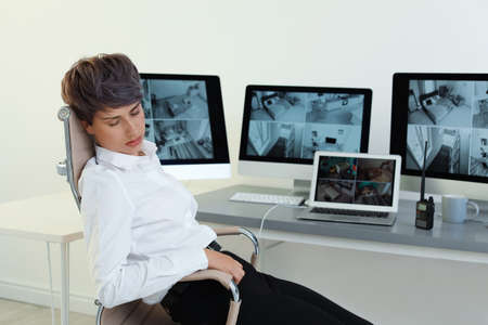 Female security guard sleeping at workplace indoors
