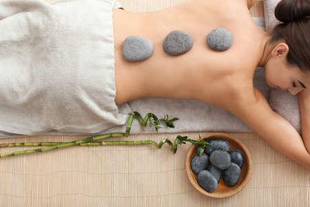 Belle jeune femme recevant un massage aux pierres chaudes dans un salon spa, vue de dessus
