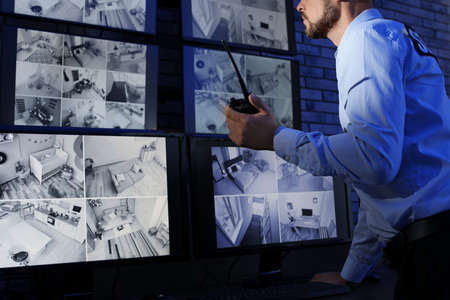 Guardia de seguridad masculino con transmisor portátil que monitorea modernas cámaras CCTV en interiores Foto de archivo