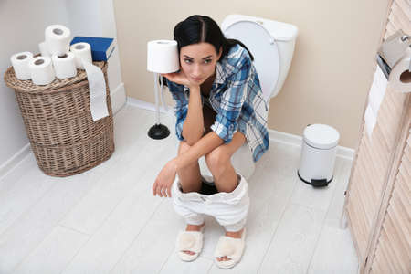 Woman with paper roll sitting on toilet bowl in bathroom Imagens