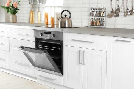 Horno moderno abierto empotrado en muebles de cocina Foto de archivo