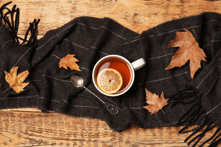 Flat lay composition with hot cozy drink, scarf and autumn leaves on wooden background