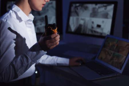 Guardia de seguridad femenino con transmisor portátil que monitorea las cámaras domésticas en interiores por la noche, primer plano