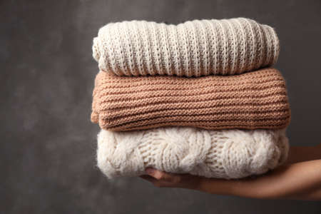 Woman holding stack of folded warm knitted sweaters against dark background