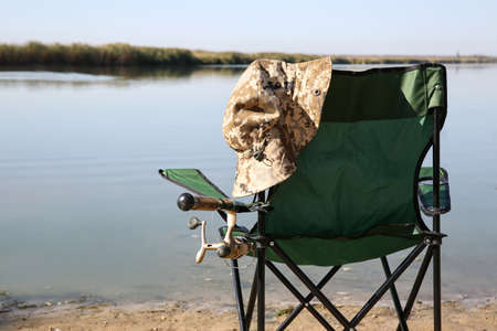 Camping chair with fishing rod at riverside on sunny day