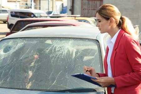 Insurance agent filling claim form near broken car outdoors Standard-Bild