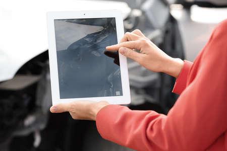 Mujer fotografiando un coche roto después de un accidente por reclamación de seguro, primer plano Foto de archivo