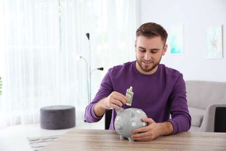 Young man putting money into piggy bank at table indoors. Space for text