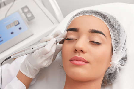 Young woman undergoing procedure of permanent eye makeup in tattoo salon