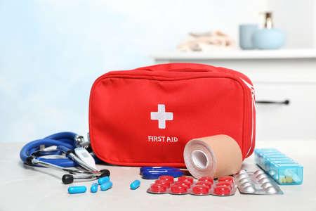 Trousse de premiers soins avec pilules sur table à l'intérieur Banque d'images