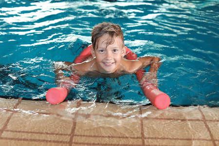 Ragazzino con la tagliatella di nuoto nella piscina coperta