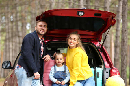 Happy young family near car trunk loaded with suitcases outdoors Stock Photo