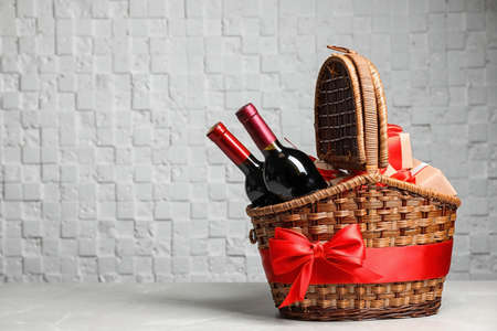 Gift basket with bottles of wine on light background. Space for text