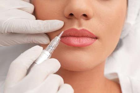 Mujer joven sometidos a procedimiento de maquillaje de labios permanente en el salón de tatuajes, primer plano Foto de archivo