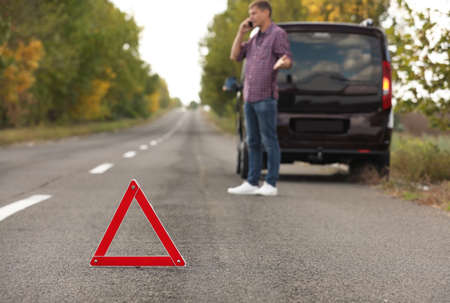 Emergency stop sign and driver near broken car on road. Auto insurance Reklamní fotografie
