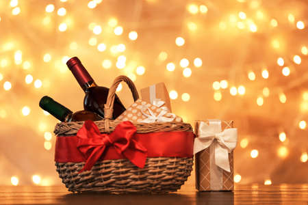 Gift basket with bottles of wine against blurred lights. Space for text