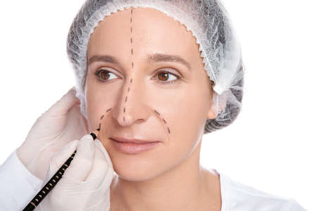 Doctor marking mature woman face before cosmetic surgery on white background