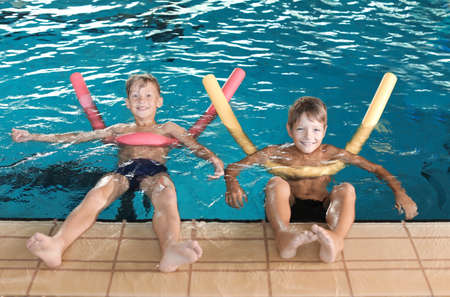 Little boys with swimming noodles in indoor pool Stockfoto