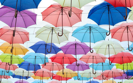Many opened multicolored umbrellas on light background