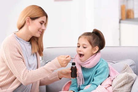 Mother giving daughter cough syrup on sofa at home Stockfoto