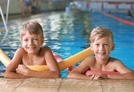 Little boys with swimming noodles in indoor pool Archivio Fotografico