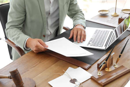 사무실 테이블에 문서와 노트북이 있는 남성 공증인, 근접 촬영 스톡 콘텐츠