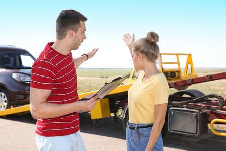 People near tow truck with broken car outdoors Stock Photo