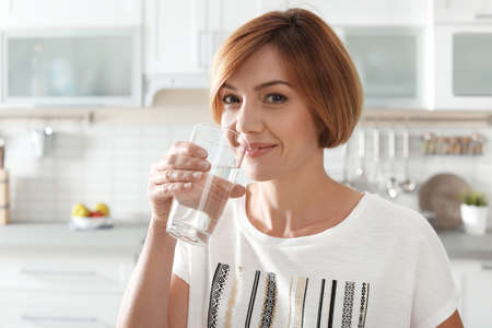 Woman drinking clean water from glass in kitchen