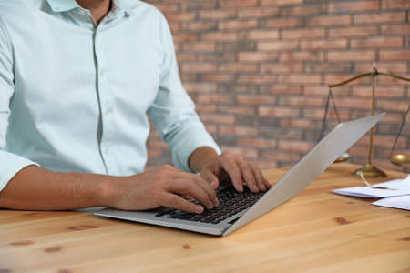 Male notary working with laptop at table in office, closeup