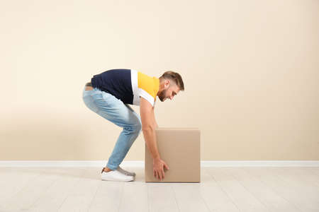 Full length portrait of young man lifting carton box near color wall. Posture concept 免版税图像