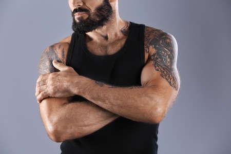 Hombre tatuado sobre fondo gris, vista de cerca Foto de archivo