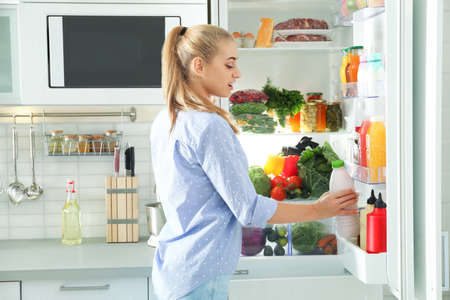 Woman taking bottle with milk out of refrigerator in kitchen