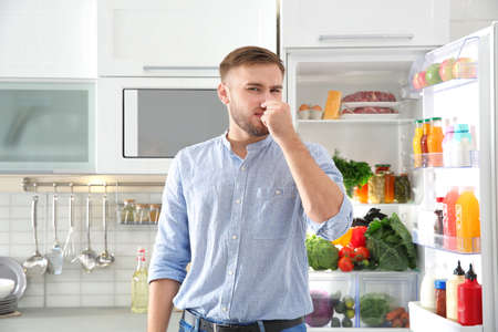 Man feeling bad smell from stale products in refrigerator at home Stock Photo