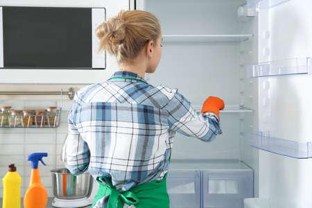 Mujer en guantes de goma limpieza de nevera vacía en casa