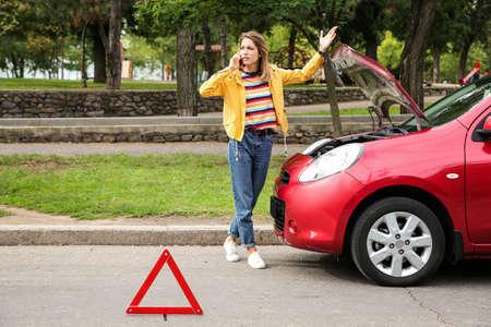 Woman talking on phone near broken car outdoors Reklamní fotografie