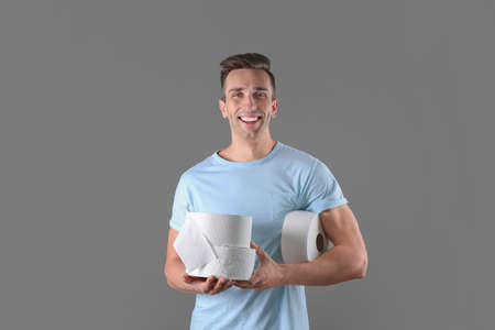 Young man holding toilet paper rolls on color background