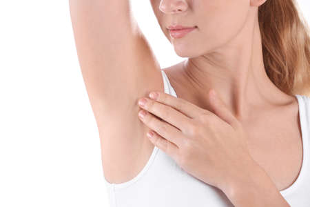Young woman showing armpit on white background, closeup. Using deodorant