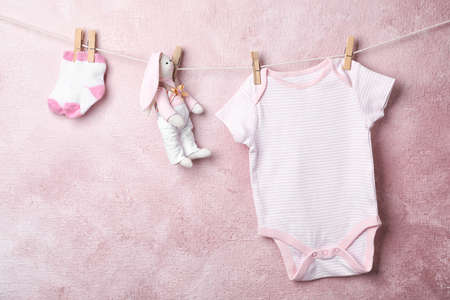 Baby clothes and toy hanging on rope near color wall. Space for text